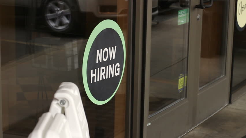 Woman walks through a door of a business with a now hiring sign in the foreground
