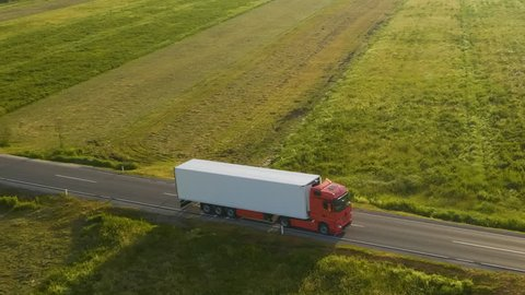 Aerial shot of a truck on the road in beautiful countryside in the summer.