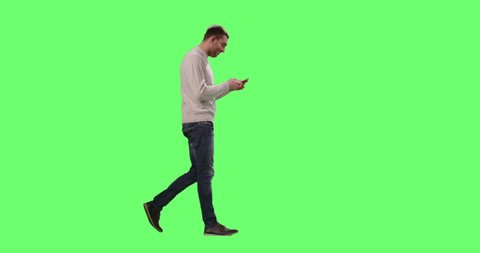 Casual Caucasian Man is Walking and Using Smart Phone on a Mock-up Green Screen in the Background. Shot on RED Cinema Camera in 4K (UHD).