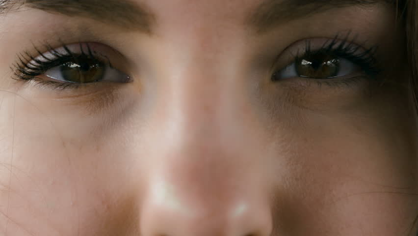 Alluring eyes of a young woman looking into the camera. Close up.