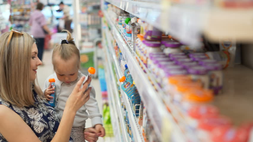 Mom with child look for child's fruit puree and juices inside of market place, smile, walking indoor between shelves, carefully think choise kids products. Beautiful wonder infant take packet at hands | Shutterstock HD Video #29345779