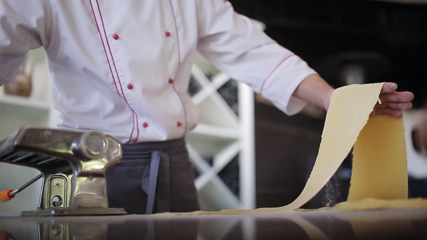 Chef's hands use a pasta cutting machine. Fresh spaghetti pasta coming out of pasta machine close-up, slow mo | Shutterstock HD Video #29346943