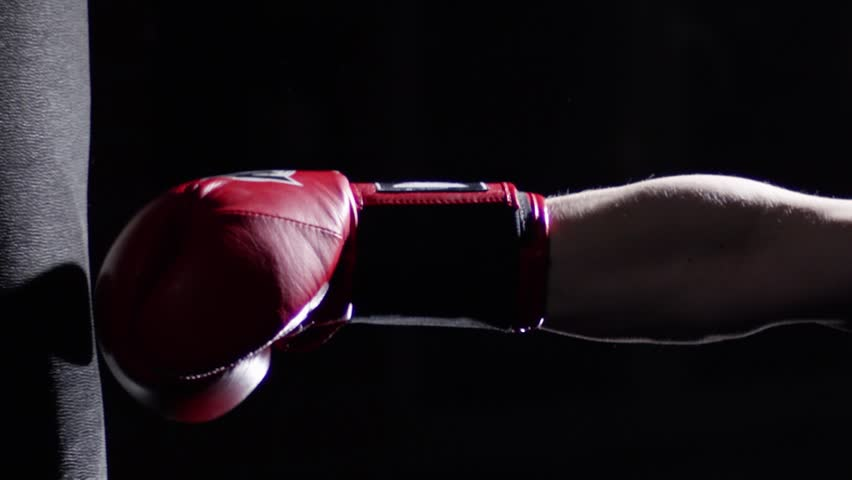 Fighter Practicing Some Kicks With Punching Bag - A Man With A Tattoo Boxing On dark Background. Kick, punching bag on dark background. Black punching bag weighs at the gym