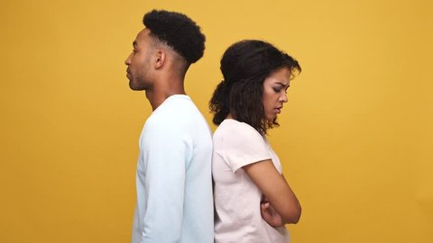 Young afro american man trying to make up a quarrel with his offended girlfriend isolated over yellow background