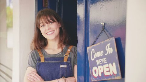 Owner Standing Arms Crossed By Open Sign On Delicatessen Door