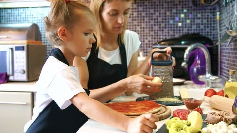 Young woman with her little adorable daughter in formal clothing making pizza in modern kitchen at home.