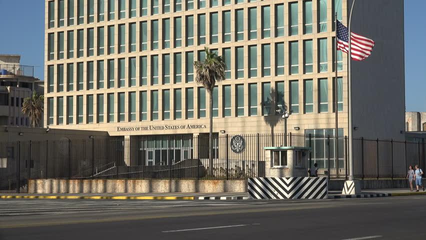 HAVANA, CUBA - FEBRUARY 2017: Security personnel and tourists walking past American embassy in Havana, Cuba