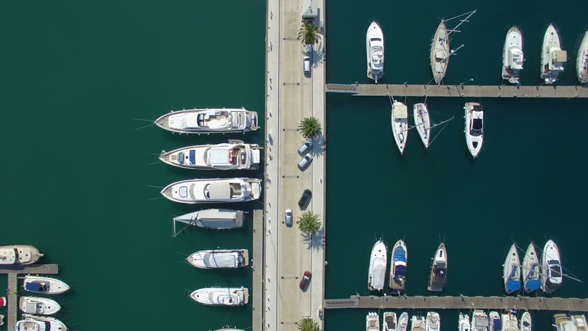 Top view aerial footage of Porto Montenegro Tivat pier with car moving among luxury yachts and sailboats.
