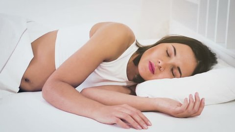 Young smiling woman sleeping with ease in bed in morning