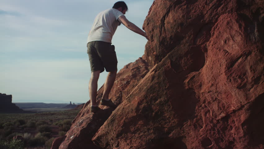 Bearded hipster man climbing red rock, rock formations in distance, Arizona or Utah desert, Summer 2017
