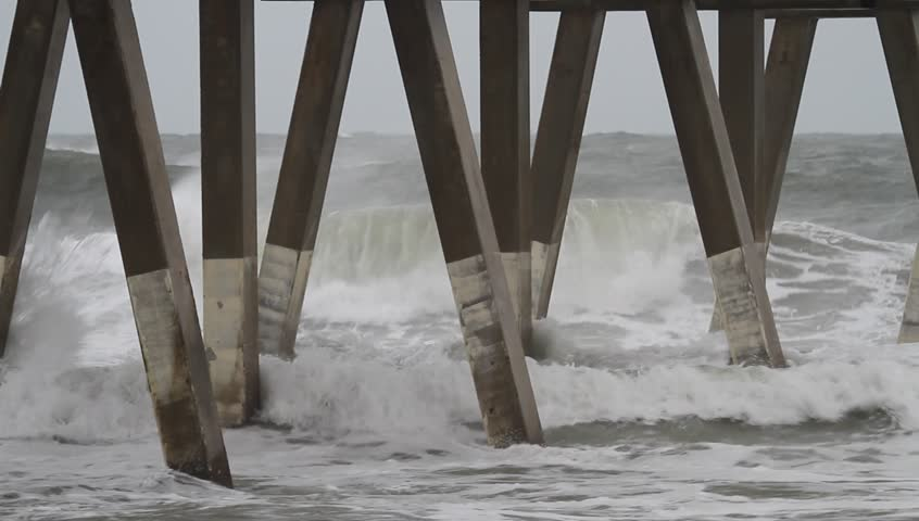 Medium Close Clip Atlantic Ocean Waves Crash into Johnny Mercer Pier Wrightsville Beach North Carolina as Hurricane Sandy Passes Along the Coast.  Waves spray up as they hit the pilings of the pier.