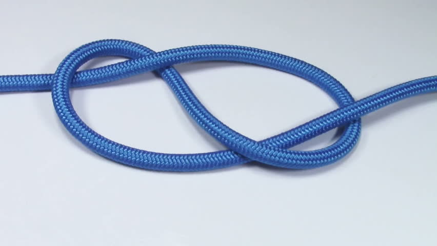 Figure eight knot made from blue synthetic rope, tightening on white background #29461750