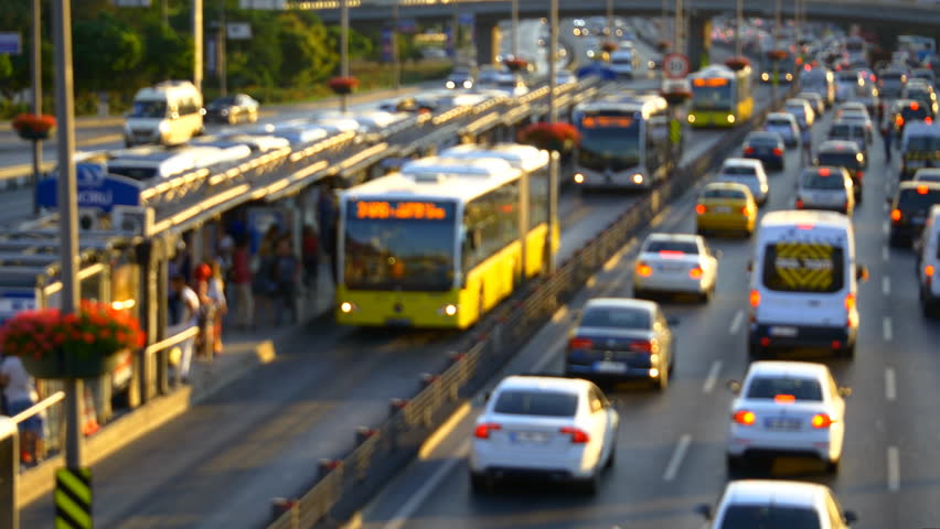 Insane rush hour traffic jam in Istanbul Metro Bus Line. High speed public buses moving on express way. Incirli bus stop with yellow buses. Out of focus.