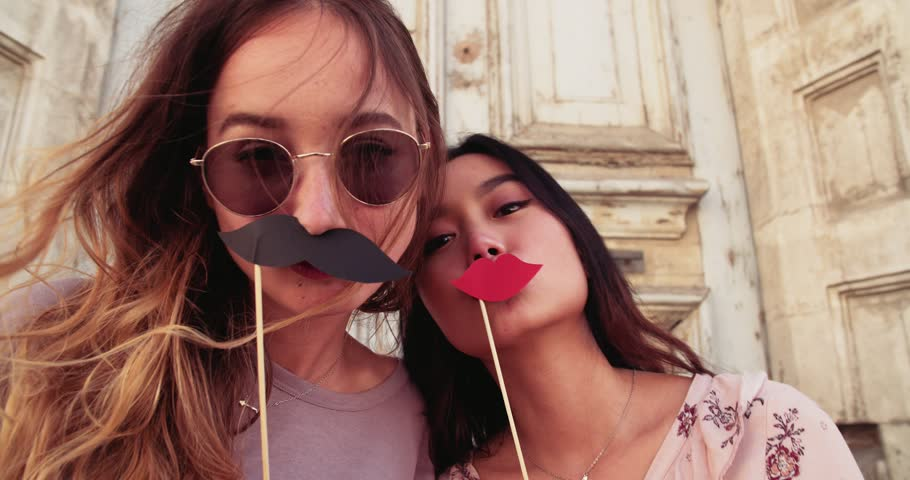 Hipster teenage girls having fun with fake mustaches and lips on sticks in old streets | Shutterstock HD Video #29472589