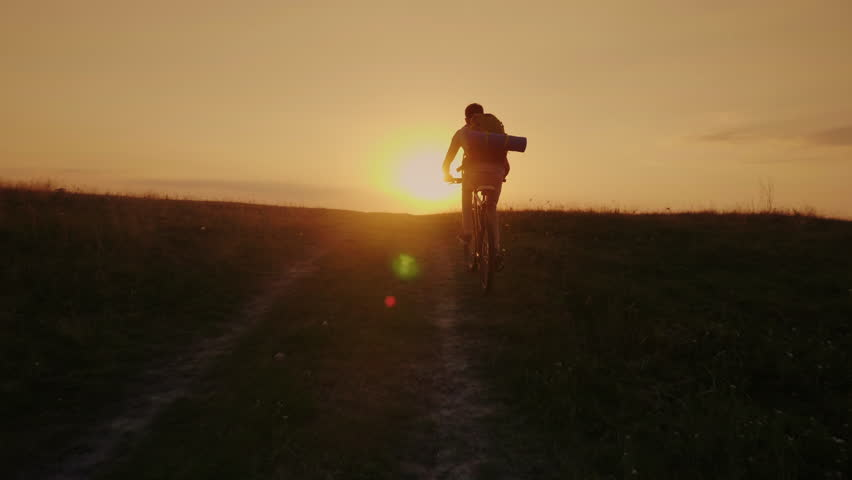 A biker with a backpack rides uphill along a rural road. In the rays of the setting sun | Shutterstock HD Video #29473189