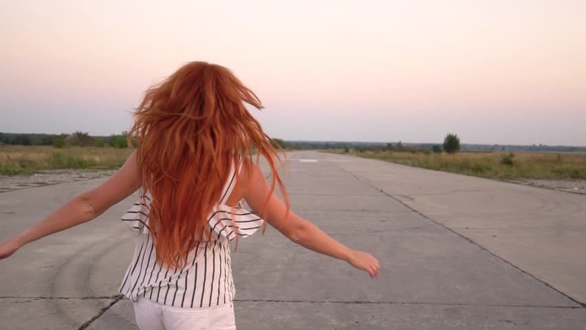 Happy red-haired woman whirls, her hair fluttering in the wind, slow motion | Shutterstock HD Video #29481829