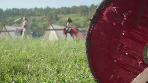 Blur of man with sward preparing for reenactment of ancient battle. Focused knight's shield on the right