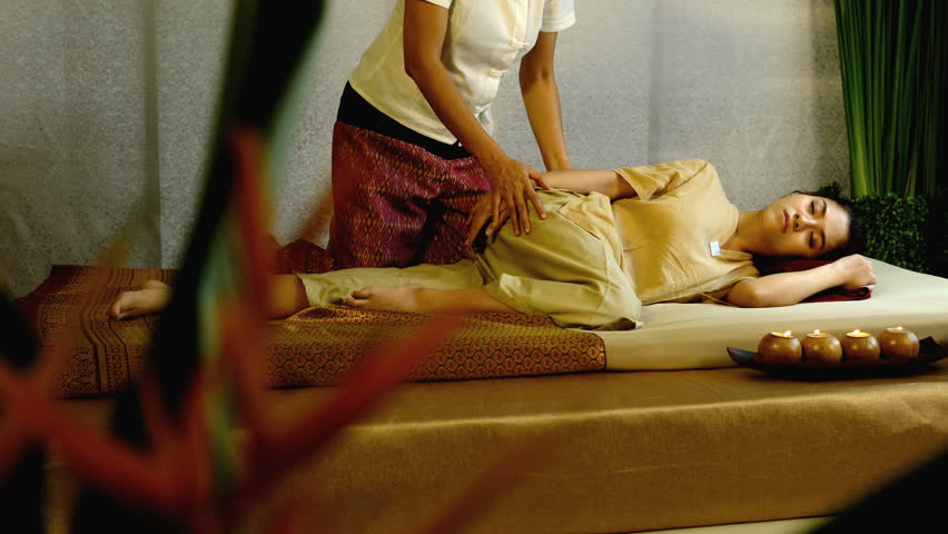 Dolly shot with Thai masseuse massage neck and shoulder of pretty woman lying on mattress pad, enjoyment and treatment of pain with traditional thai therapy, Thai massage concept