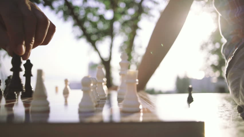 Grandfather and grandson are playing chess in park, slow motion, close up