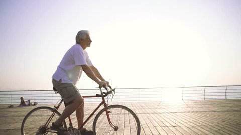 Handsome senior man riding bike on seafront, slow motion