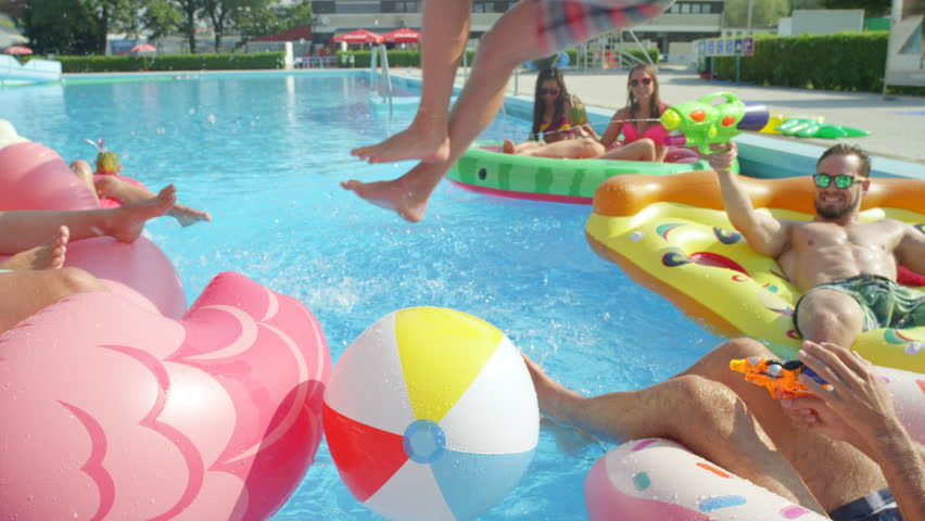SLOW MOTION CLOSEUP Smiling young people partying on floaties and jumping into pool. Happy teenagers having watergun fight splashing water on inflatable pizza, flamingo, watermelon and doughnut floats
