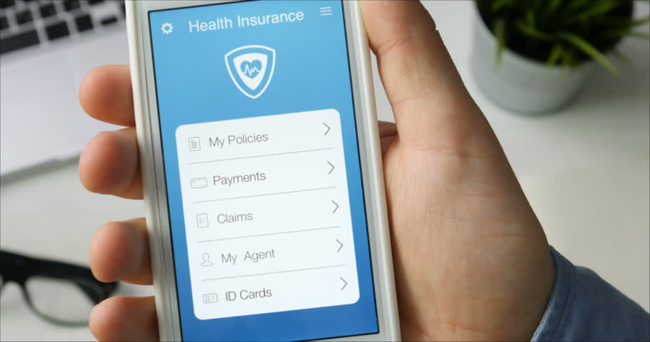 Paying for health insurance using smartphone app sitting at the desk | Shutterstock HD Video #29520859