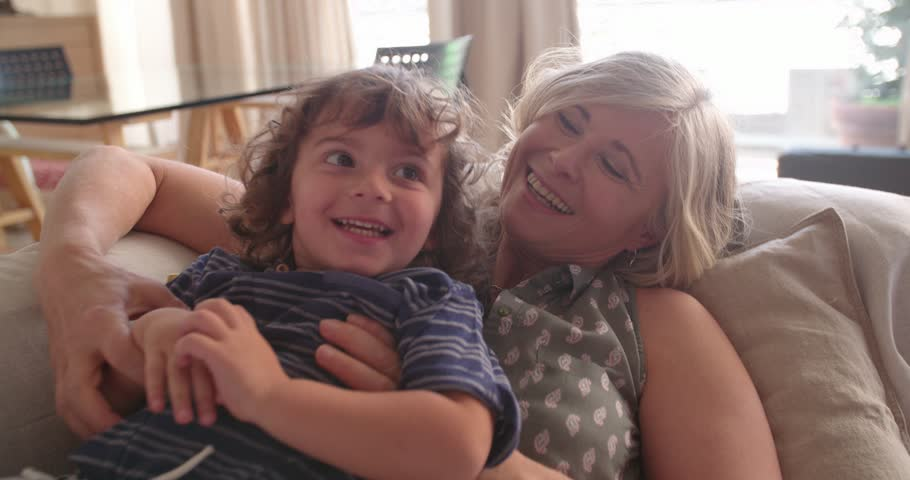 Beautiful grandma having fun hugging, laughing and playing with cute curly grandson at home