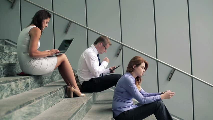 Young business people working on stairs by office building