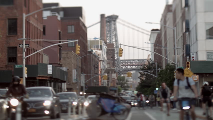 Williamsburg bridge between buildings on Kent Ave. Williamsburg, New York. Car Traffic. Cyclists on bike lane. People walking and jogging. Apartment Buildings. Urban area. Tilt-shift lens used.
