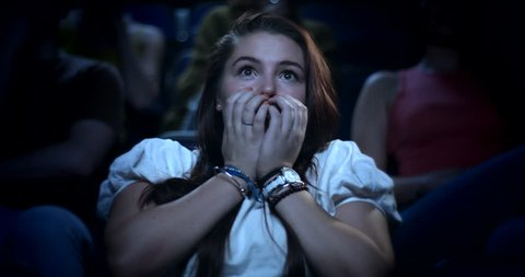 Frightened woman watching a horror film. Jumps at a scary moment