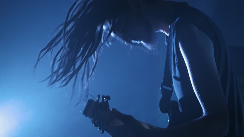Guitarist rocker with dreadlocks playing the electric guitar on stage. Performance music video rock, punk, heavy metal band in slow motion.