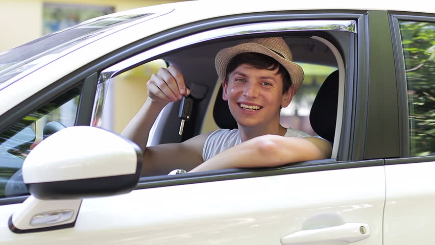 Young man holding keys to new car auto and smiling at camera