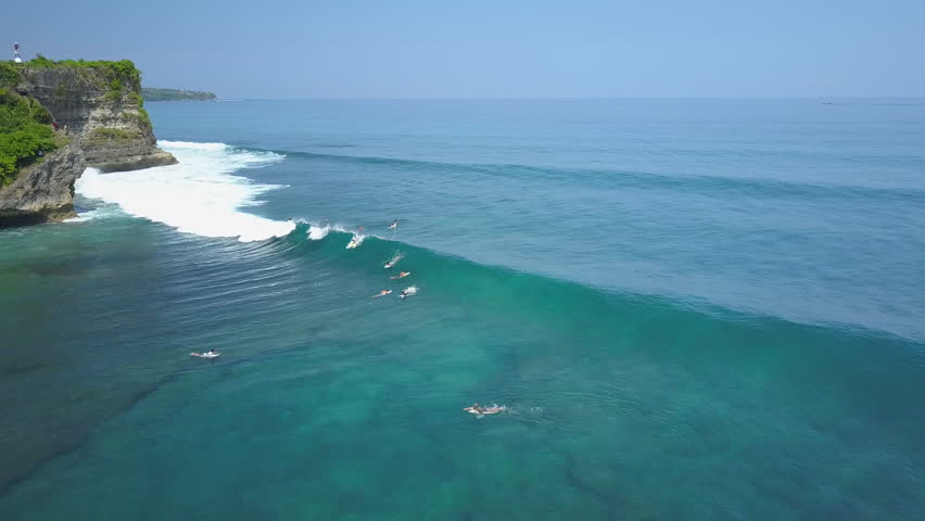 AERIAL: Beginners and pro surfers waiting in lineup trying to catch a breaking wave in crowded sunny Bali. Unrecognizable people on summer vacation swimming, paddling & surfing in crystal clear sea
