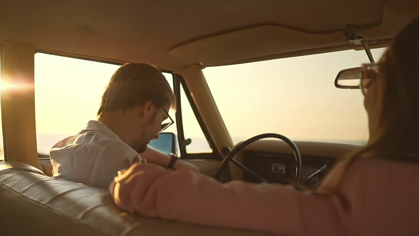 Beautiful young lovers in sunglasses sitting in retro car and talking  | Shutterstock HD Video #29695639