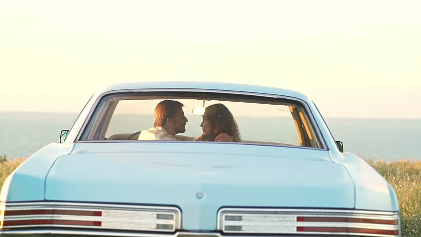Back view of young pretty lovers talking and kissing in retro car near sea