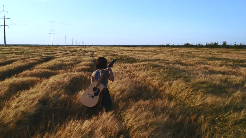 Girl walking with a guitar at wheat field.