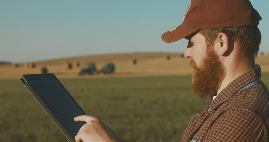 Modern farming concept, advanced technology in agriculture. Male farmer with portable tablet computer in a field using specialized app. 4K UHD 60 FPS