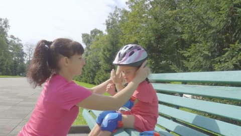 Mother helps his daughter to wear a helmet and protective gear, for roller skating in the park. Woman helps girl put on protective knee and elbow pads. Active family rest in the park.