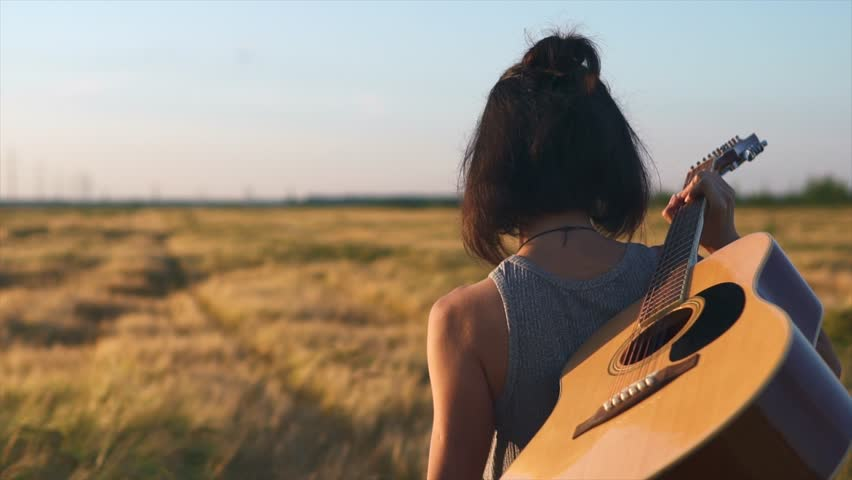 Girl walking alone with a guitar at wheat field