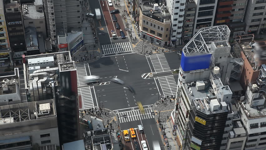 Aerial View of Busy Tokyo Car Traffic Japanese Asian Intersection, Japan, Commute, Crosswalk Crossroad, Metropolitan Area, time lapse, Blurred Logos People Pedestrians Crossing Walking Passing,