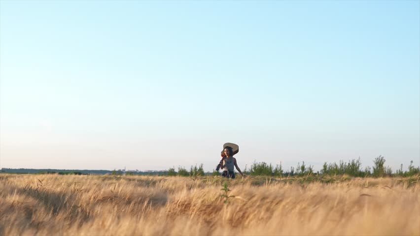 Beautiful girl walking with a guitar at wheat field