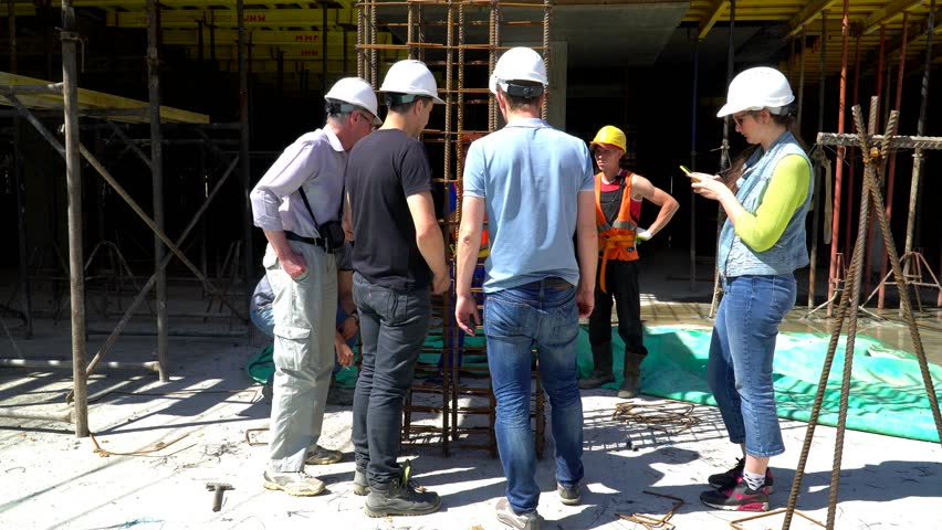 20 July 2017. Russia. Moscow. Construction site. The construction of the building from monolith reinforced concrete. Discussion the reinforcement cage of the column.