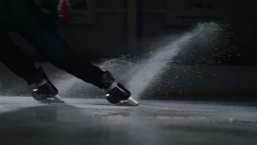 Hockey player make ice sparkles on high speed braking. Motion blur. Legs view only, hockey stick in hands, canadian tricks