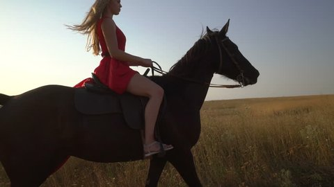 Young blonde girl horseback rider in red dress riding horse on country road. Side view of horsewoman with her black stallion walking across dry grass field in the evening. Gimbal steadicam shot.