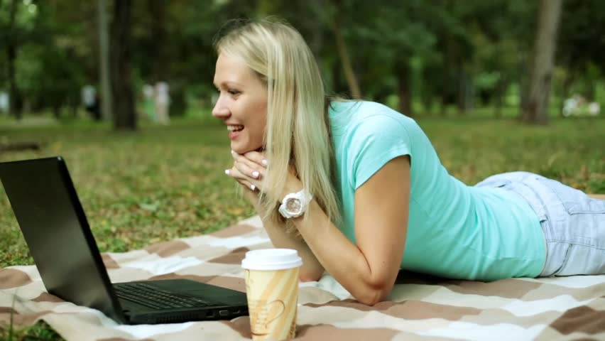 Young woman with laptop on the grass. The girl is talking on skype using a laptop in the park. | Shutterstock HD Video #29797039