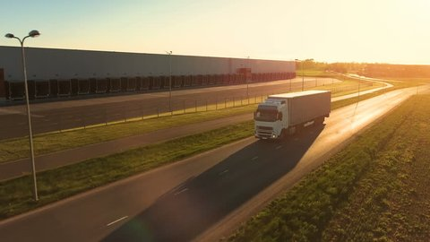 Aerial View of White Semi Truck with Cargo Trailer Moving on the Highway. In the Background Warehouses and Rural Area, Sun is Setting. Shot on Phantom 4K UHD Camera.