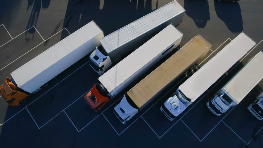 Aerial Top View of White Semi Truck with Cargo Trailer Parking with Other Trucks on Special Parking Lot. Shot on Phantom 4K UHD Camera.