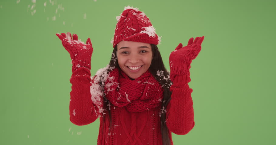 Happy smiling Hispanic girl in bright red winter clothes covered in snow on green screen. On green screen to be keyed or composited.