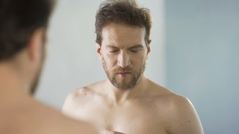 Middle-aged man critically looking at his beard in mirror, morning ritual