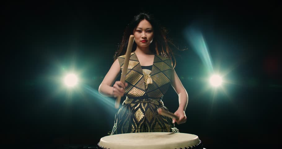 epic performance of Asian girl drumming Taiko , concert light, Slow motion